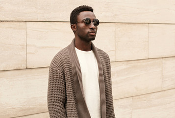 Wall Mural - Stylish african man model wearing brown knitted cardigan, sunglasses on city street over brick wall background