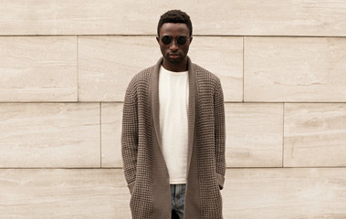 Wall Mural - Stylish african man wearing brown knitted cardigan, sunglasses, male model posing on city street over brick wall background