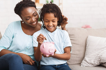 African american family inserting money to piggybank