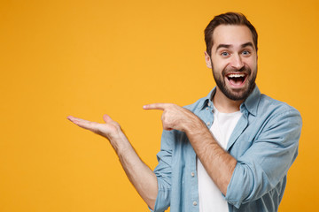 Excited young bearded man in casual blue shirt posing isolated on yellow orange background, studio portrait. People emotions lifestyle concept. Mock up copy space. Pointing index finger, hand aside.