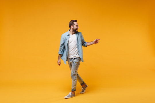 Excited young bearded man in casual blue shirt posing isolated on yellow orange background studio portrait. People emotions lifestyle concept. Mock up copy space. Looking, pointing index finger aside.
