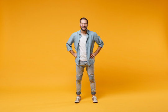 Cheerful young bearded man in casual blue shirt posing isolated on yellow orange background, studio portrait. People emotions lifestyle concept. Mock up copy space. Standing with arms akimbo on waist.