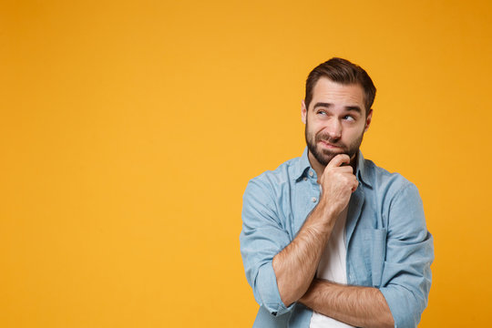 Pensive young bearded man in casual blue shirt posing isolated on yellow orange background studio portrait. People emotions lifestyle concept. Mock up copy space. Put hand prop up on chin, looking up.
