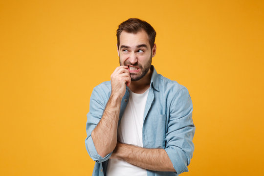 Pensive puzzled young bearded man in casual blue shirt posing isolated on yellow orange background, studio portrait. People emotions lifestyle concept. Mock up copy space. Gnawing nails, looking up.
