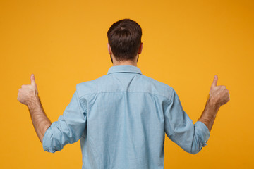 Back rear view of young bearded man in casual blue shirt posing isolated on yellow orange...