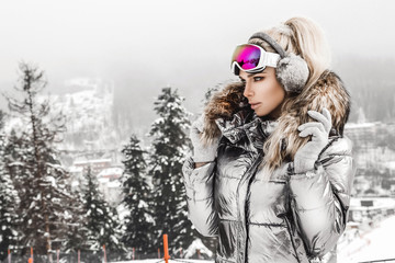 Young woman winter portrait. Winter fashion model with ski suit and goggles. Attractive young woman in wintertime outdoor. Mountains, white snow in magic winter day. Wall mural