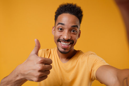Close up of young african american guy in casual t-shirt posing isolated on yellow orange background. People lifestyle concept. Mock up copy space. Doing selfie shot on mobile phone, showing thumb up.