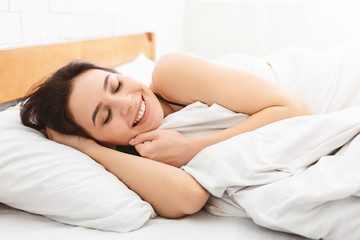 Well-slept woman lying in bed, free space