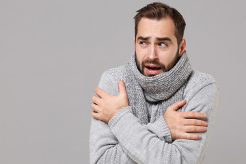 Fototapeta Frozen young man in gray sweater posing isolated on grey wall background, studio portrait. Healthy fashion lifestyle, cold season concept. Mock up copy space. Holding hands folded, huging himself. obraz