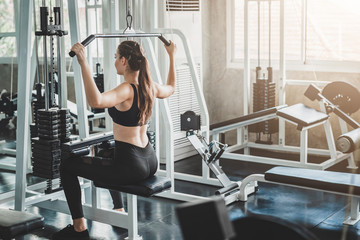 Woman doing lat pull pull down exercise in fitness gym Wall mural