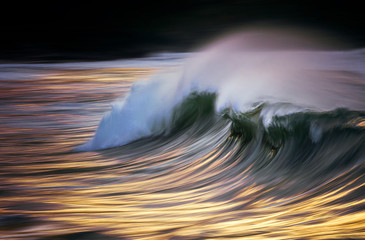 Photo of a wave breaking at sunset with in camera panning technique