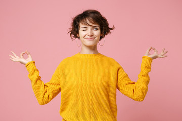Obraz Funny young brunette woman girl in yellow sweater posing isolated on pastel pink background. People lifestyle concept. Mock up copy space. Hold hands in yoga gesture relaxing meditating looking aside. - fototapety do salonu