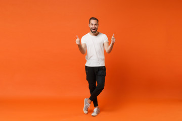Cheerful excited young man in casual white t-shirt posing isolated on bright orange wall background studio portrait. People sincere emotions lifestyle concept. Mock up copy space. Showing thumbs up. Wall mural