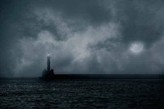 Lonely lighthouse on stormy sea against dark clouds