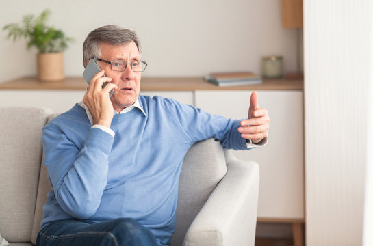 Senior Man Talking On Cellphone Sitting On Couch At Home
