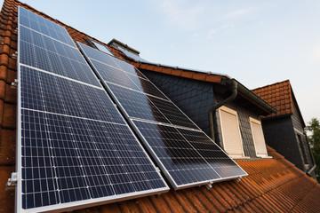 Solarpanels auf Hausdach mit Gaube im Hintergrund