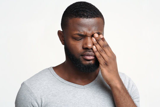 Sad black guy touching his eye, suffering from conjuctivitis