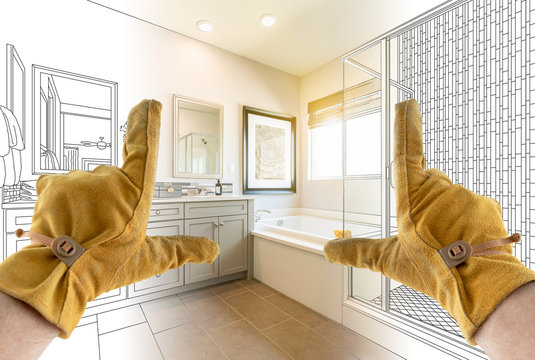 Male Contractor Hands Framing Completed Section of Bathroom Over Bathroom Drawing