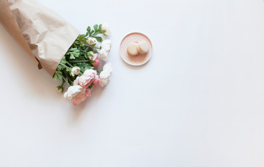 Acrylic Prints Macarons Pires cor de rosa com dois macarons ao lado de buquê de flores rosas embrulhado por um pacote de papel pardo sobre uma mesa branca visto do topo. Tons pastéis.