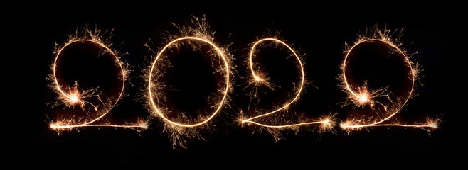 Happy New Year 2022. Number 2022written sparkling sparklers isolated on black background With Copy Space For Text. Beautiful Glowing overlay template for holiday greeting card.