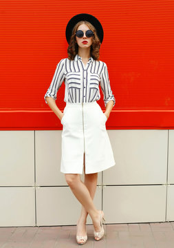 full-length beautiful young woman model wearing white striped shirt, skirt, black round hat on city street over red wall background