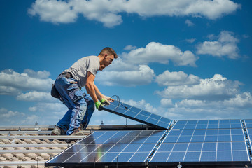 Installing solar photovoltaic panel system. Solar panel technician installing solar panels on roof....