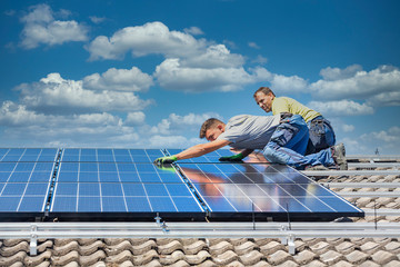 Installing solar photovoltaic panel system. Solar panel technician installing solar panels on roof. Alternative energy ecological concept. Fotoväggar
