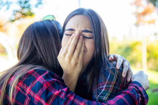 Two sad best female friends embracing each other