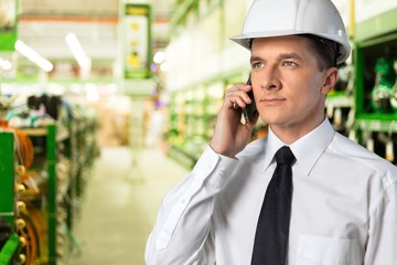 Business man in white hard hat and mibile phone