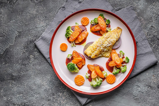 Top view fillet of sea bass with vegetables. Baked fish, cauliflower and carrots on a big plate. Copy space