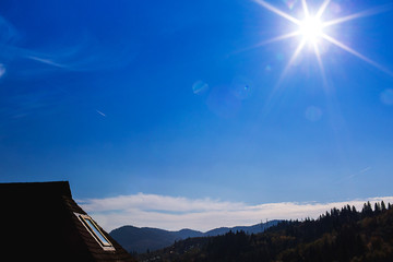 Foto auf Leinwand Dunkelblau House with wooden tiles in mountain landscape on sunny day. Wooden building on background of mountain forest.