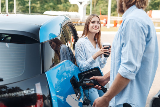 Traveling. Young couple traveling by electric car stopping at charging station boyfriend plugging in cable talking with girlfriend drinking hot coffee joyful