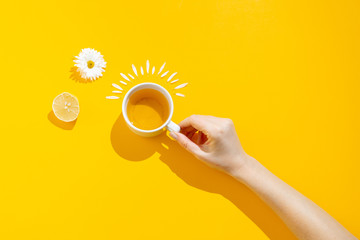 Foto op Plexiglas Thee Hot drink, cup of tea with chamomile and lemon on a yellow background