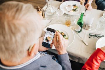 Senior man taking picture of food in restaurant