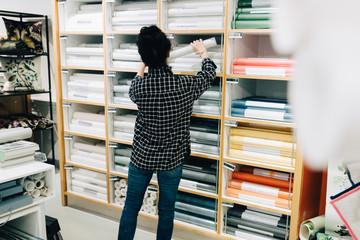 Rear view of senior saleswoman arranging wallpapers in rack