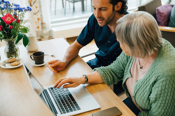 Confident male caregiver assisting senior woman doing online shopping with credit card and laptop in nursing home