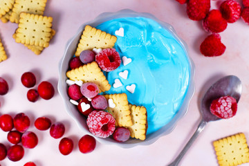 Healthy yogurt and fruit smoothie bowl with natural blue spirulina powder topped with red raspberry cranbery and small biscuits