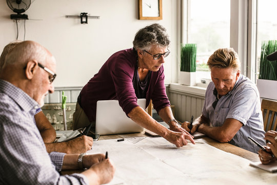 Female instructor explaining senior men over map at table during navigation course