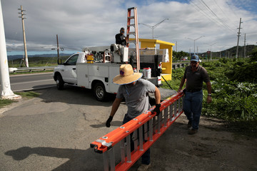 Men carry a ladder as they work fixing power lines after an earthquake in Guanica