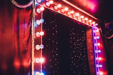 Light Bulbs On Stage Theatrical scene with colored glitter neon bulbs for presentation or concert performance. Night show in festive evening.