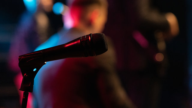 Mic on stand with people performing in the background.