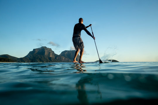 man Stand Up paddle boarding on Calm sea water Lord Howe Island