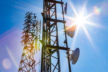 Bright sun shine over two cell site towers, radio and GPS transmitter and receiver, associated with electromagnetic pollution, with vibrant lens flare