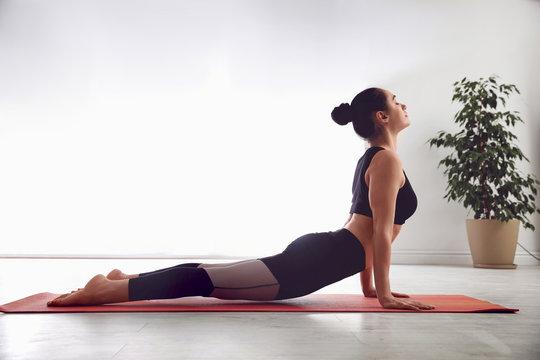 Woman practicing cobra asana in yoga studio. Bhujangasana pose