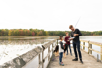 Father fishing with two young boys at lake