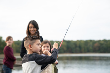 Young boy fishing with his family