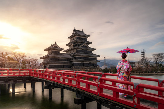 Young asian woman wearing Kimono Japanese tradition dressed sightseeing at Matsumoto Castle during cherry blossom (Sakura) is one of the most famous sights in Matsumoto, Nagano, Japan.