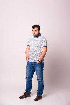 Portrait of a bearded man in loose clothing in full growth on a white background.