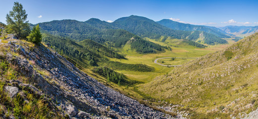 Fototapete - Panoramic view from the mountain pass to the valley. Sunny summer day. Travel and vacation in the mountains.