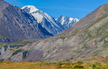 Fototapete - Mountain view, sunny day. Snow-capped peaks, gorge. Traveling in the mountains, climbing.